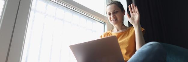 Giovane donna saluta con la mano al laptop mentre è seduta sul davanzale della finestra