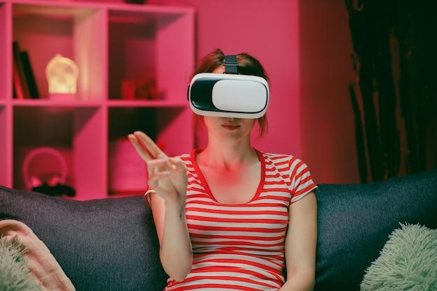 La giovane donna indossa le cuffie vr e tocca lo schermo virtuale di notte.