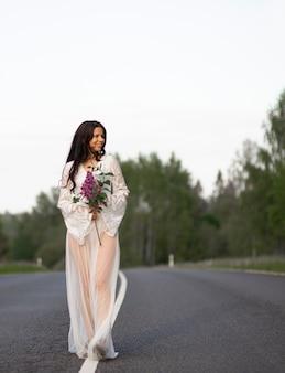 La giovane donna indossa il vestito bianco che tiene il fiore lilla sulla strada campestre vuota