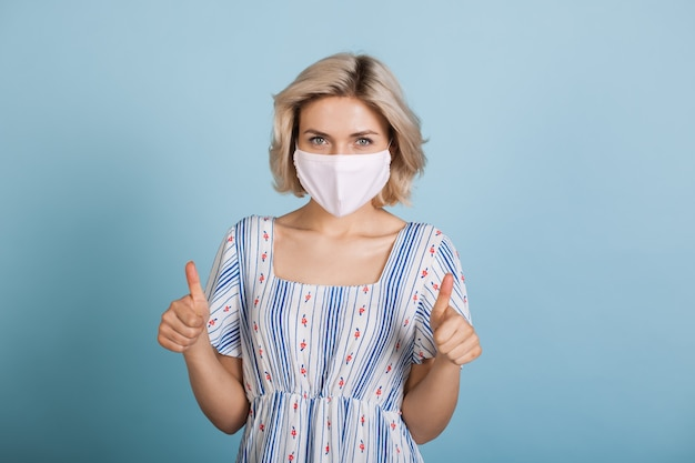 Giovane donna che indossa una maschera antinfluenzale e vestito mentre gesticola il segno simile su una parete blu dello studio