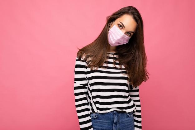 Giovane donna che indossa una maschera di protezione antivirus per prevenire l'infezione da corona covid-19 e sars cov 2 isolata su sfondo rosa. copia spazio