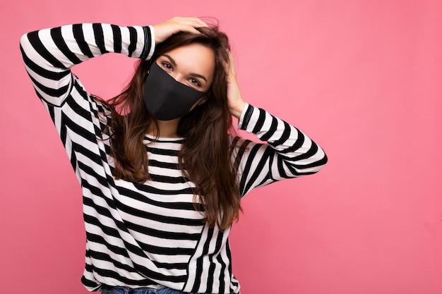 Giovane donna che indossa una maschera di protezione antivirus per prevenire l'infezione da corona covid-19 e sars cov 2 isolata su sfondo rosa.