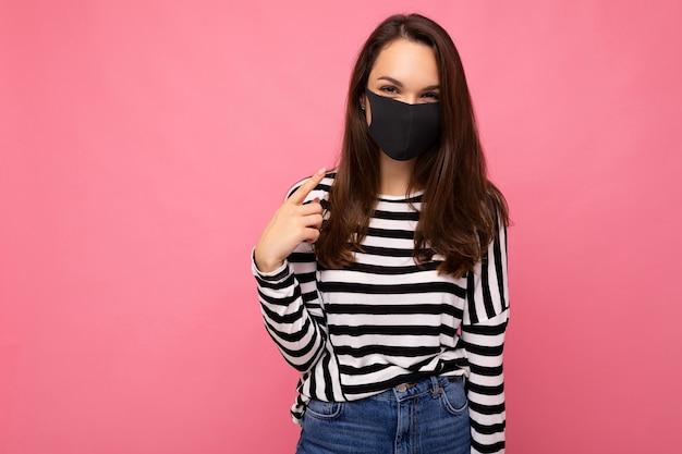 Giovane donna che indossa una maschera di protezione antivirus per prevenire l'infezione da corona covid-19 e sars cov 2 isolata su sfondo rosa