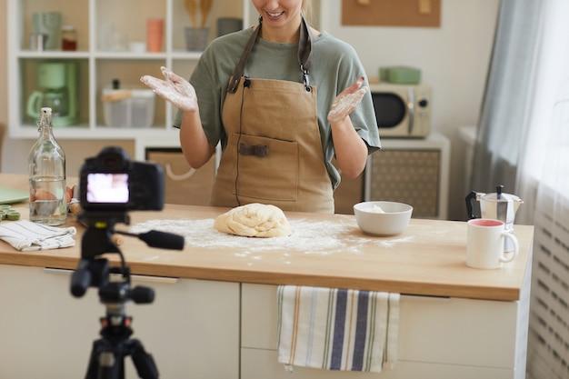 Giovane donna che indossa il grembiule in piedi in cucina e fare la pasta per la torta e girare il video per il contenuto
