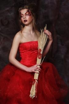 Giovane donna che indossa un abito da ballo con trucco luminoso che tiene rami secchi