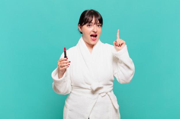 Giovane donna che indossa un accappatoio che si sente un genio felice ed eccitato dopo aver realizzato un'idea, alzando allegramente il dito, eureka!