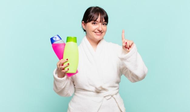 Giovane donna che indossa accappatoio sorridente e dall'aspetto amichevole, mostrando il numero uno o il primo con la mano in avanti, conto alla rovescia