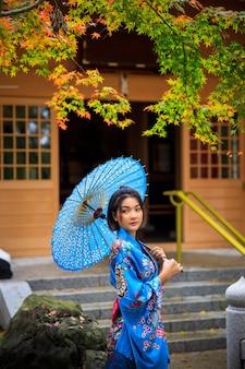 La giovane donna che indossa il kimono blu e l'ombrello ha fatto una passeggiata nel parco nella stagione delle foglie di autunno in giappone