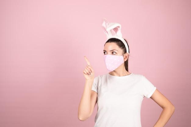 Giovane donna che indossa orecchie da coniglio e maschera protettiva in piedi sul rosa