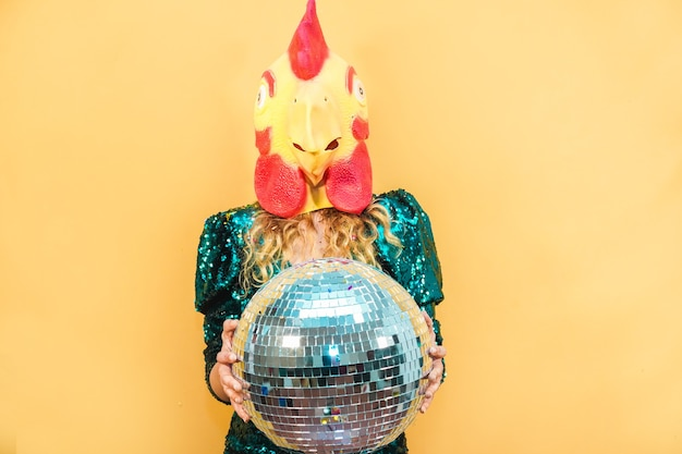 Giovane donna che indossa la maschera di pollo mentre si tiene la palla da discoteca alla festa di capodanno - soft focus sul viso