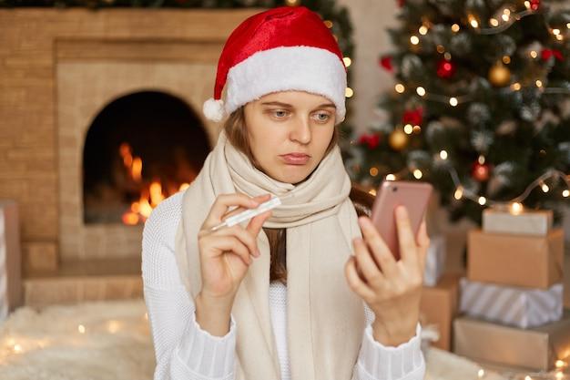 Giovane donna che indossa il cappello di natale, risponde alle videochiamate durante la pandemia del coronavirus, con l'albero di natale e il caminetto, mostra il termometro alla telecamera, raccontando la sua temperatura elevata.