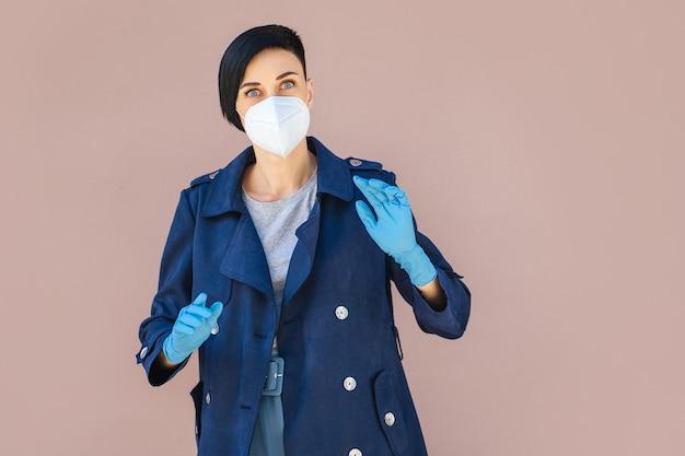 Giovane donna che indossa maschera medica monouso e guanti per strada durante l'epidemia di covid 19. protezione nella prevenzione per il coronavirus