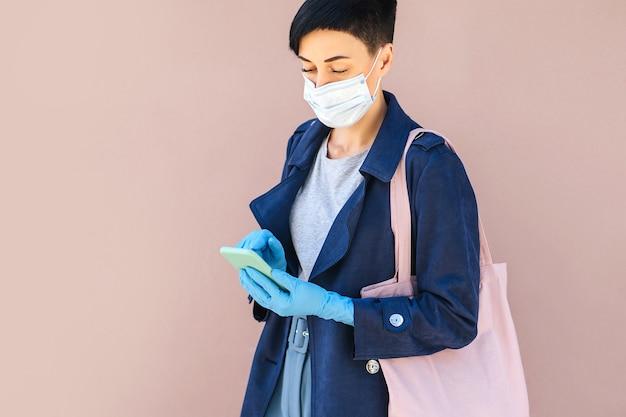 Giovane donna che indossa maschera medica monouso e guanti utilizzando smartphone per strada durante l'epidemia di covid 19. protezione nella prevenzione del coronavirus. un concetto di consegna, servizio online, app.