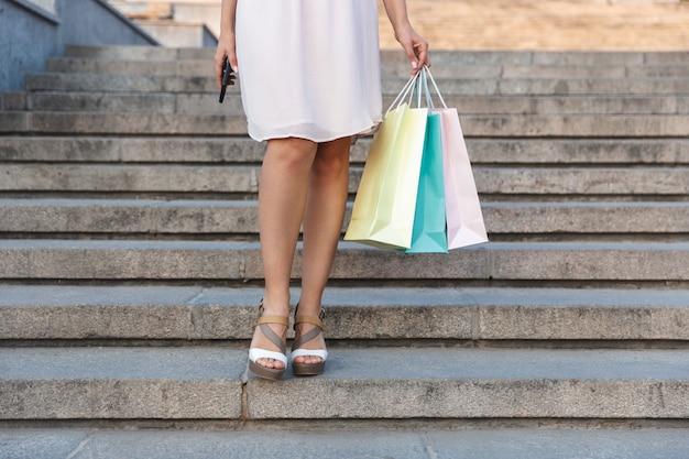 Giovane donna che indossa un abito e tenendo le borse della spesa