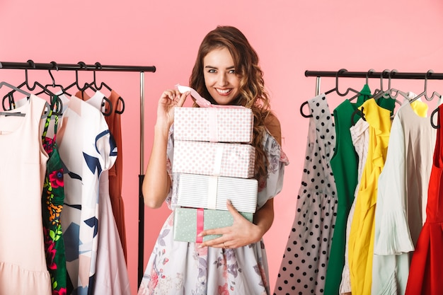Giovane donna che indossa un abito in piedi in negozio vicino appendiabiti con scatole presenti isolato sul rosa