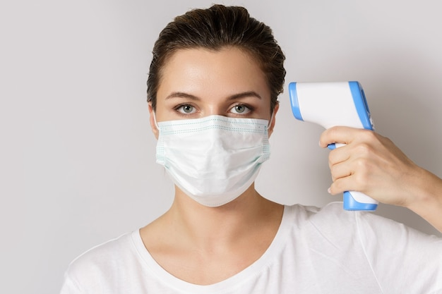 La giovane donna che indossa la maschera sta misurando la temperatura corporea con un termometro digitale a infrarossi