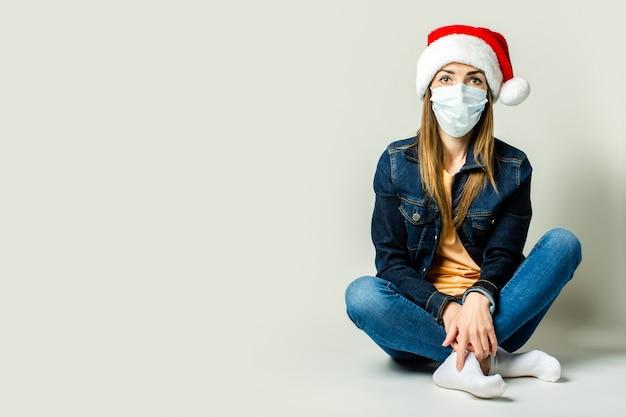 Giovane donna che indossa una maschera e un cappello di babbo natale su uno sfondo chiaro