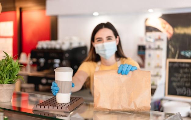 Giovane donna che indossa la maschera per il viso mentre serve la colazione da asporto e caffè all'interno della caffetteria