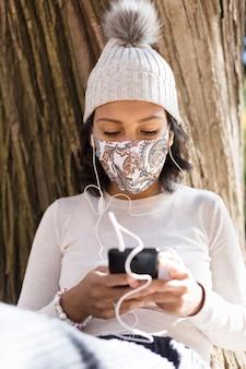 Giovane donna che indossa una maschera e un cappello di lana che ascolta la musica sul suo telefono cellulare.