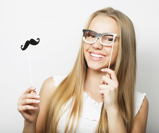 Giovane donna che indossa baffi finti. pronto per la festa.