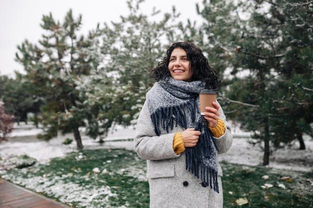 Giovane donna che indossa cappotto di moda frey e sciarpa blu sta con un caffè per andare in un parco innevato d'inverno.