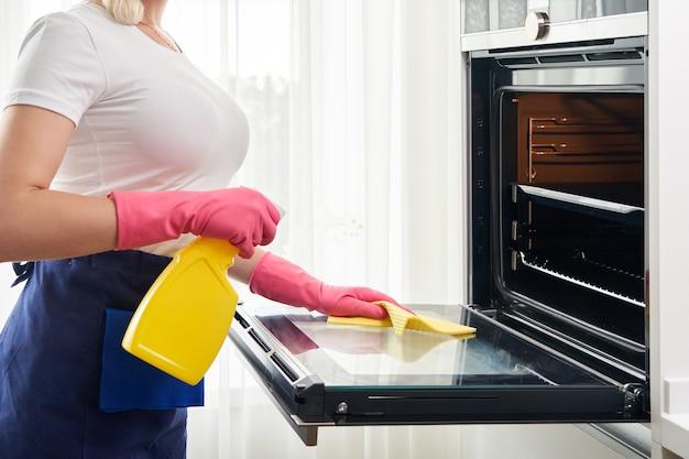 Giovane donna che indossa guanti pulizia forno in cucina. concetto di servizio di pulizia