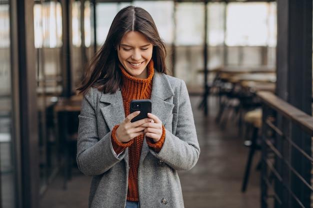 Giovane donna che indossa cappotto grigio e cammina per strada e utilizzando il telefono