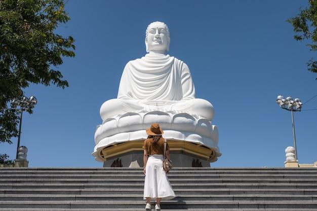 Giovane donna che indossa il cappello in piedi sulle scale con il grande buddha e il cielo blu nel tempio pagoda di long son a nha trang, vietnam