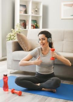 Giovane donna che indossa le cuffie che si esercita con il manubrio sul materassino yoga davanti al divano in soggiorno
