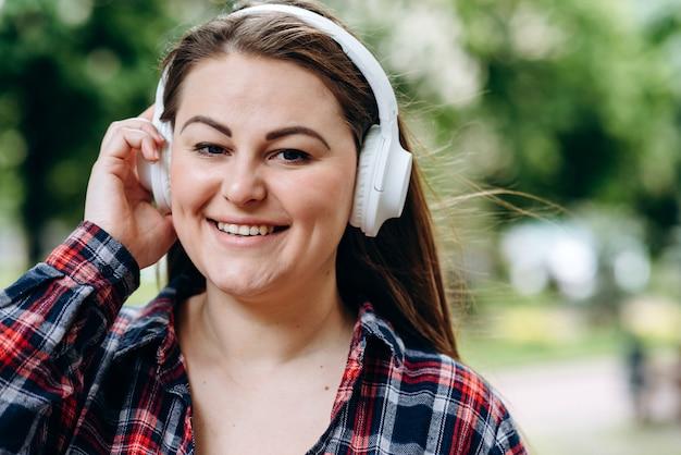 Cuffie da portare della giovane donna con una faccia felice che si leva in piedi nel mezzo del parco