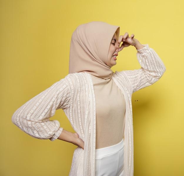 Giovane donna che indossa l'hijab con un'espressione di odore odorante che tiene un naso isolato su sfondo giallo