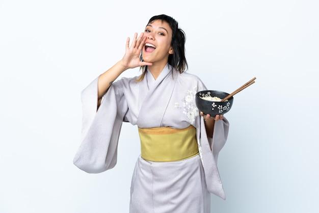 Kimono d'uso della giovane donna che tiene una ciotola di tagliatelle sopra la parete bianca che grida con la bocca spalancata