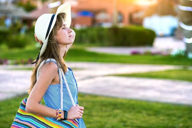 Giovane donna che indossa abito estivo azzurro e cappello di paglia giallo che tiene borsa a tracolla alla moda in piedi fuori godendo il clima caldo nel parco estivo al tramonto