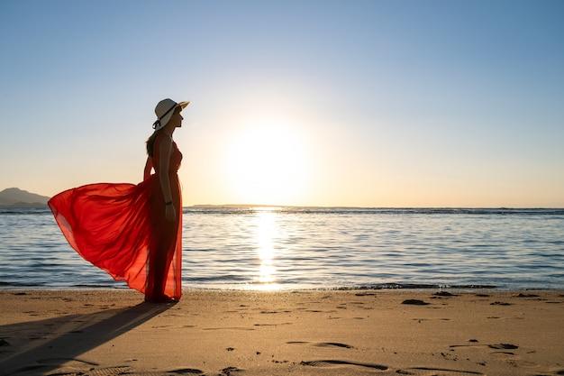 Giovane donna che indossa abito rosso lungo e cappello di paglia in piedi sulla spiaggia di sabbia in riva al mare godendo la vista del sol levante in mattinata d'estate