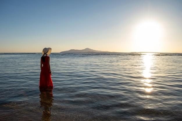 Giovane donna che indossa abito rosso lungo e cappello di paglia in piedi in acqua di mare in spiaggia godendo la vista del sol levante nella mattina di inizio estate.