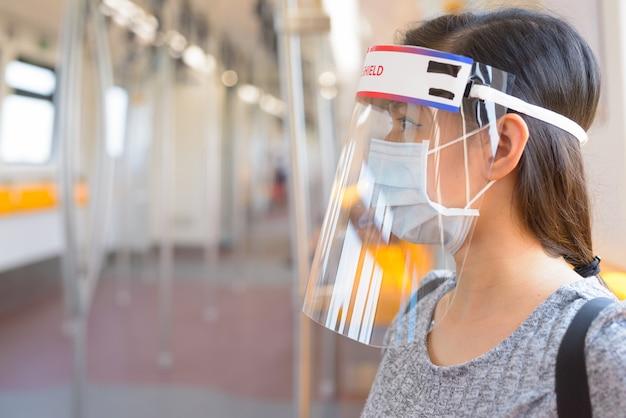 Giovane donna che indossa una maschera e una protezione per il viso all'interno del treno per la protezione dall'epidemia di virus corona