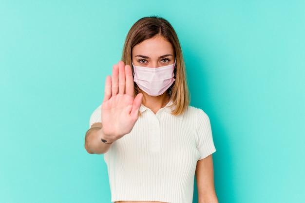 Giovane donna che indossa una maschera per virus isolato sulla parete blu in piedi con la mano tesa che mostra il segnale di stop, impedendoti.