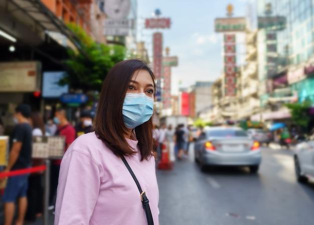 Giovane donna che indossa una maschera a yaowarat road per la prevenzione della pandemia di virus covid-19 nella chinatown di bangkok.