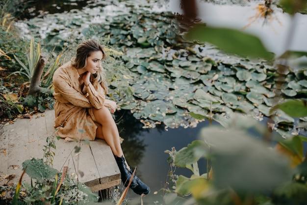 Giovane donna che indossa un maxi abito in chiffon seduto su un molo in legno vicino a un laghetto con ninfee