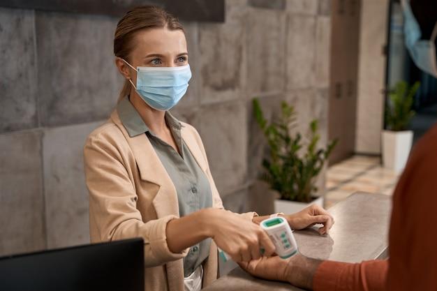 Giovane donna che indossa una maschera medica in piedi alla reception e usa un termometro a infrarossi per