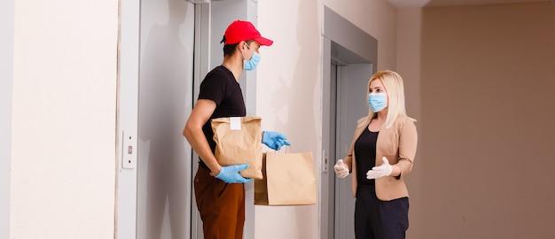 Giovane donna che indossa una maschera medica che riceve cibo ordinato dal ristorante dall'uomo delle consegne al chiuso. prevenzione della diffusione del virus
