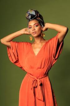 Giovane donna che indossa un abito arancione con turbante e gioielli etnici