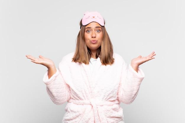 Giovane donna che indossa il pigiama, sentendosi perplessa e confusa, dubitando, soppesando o scegliendo diverse opzioni con un'espressione divertente