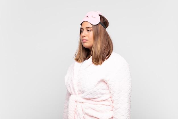 Giovane donna che indossa un pigiama, sulla vista di profilo cercando di copiare lo spazio davanti, pensare, immaginare o fantasticare