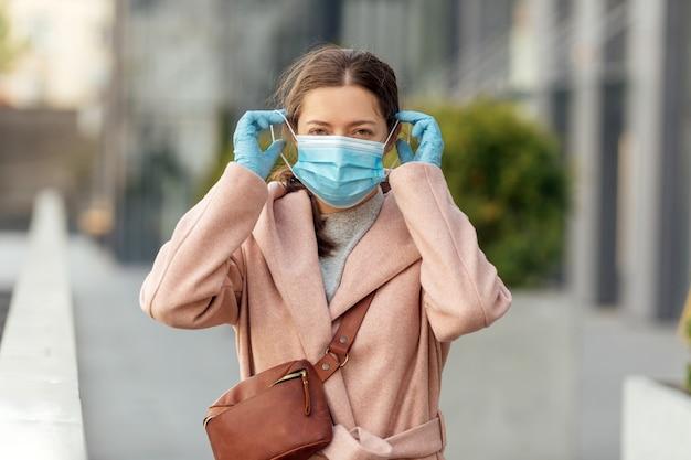 Giovane donna che indossa la maschera protettiva all'aperto