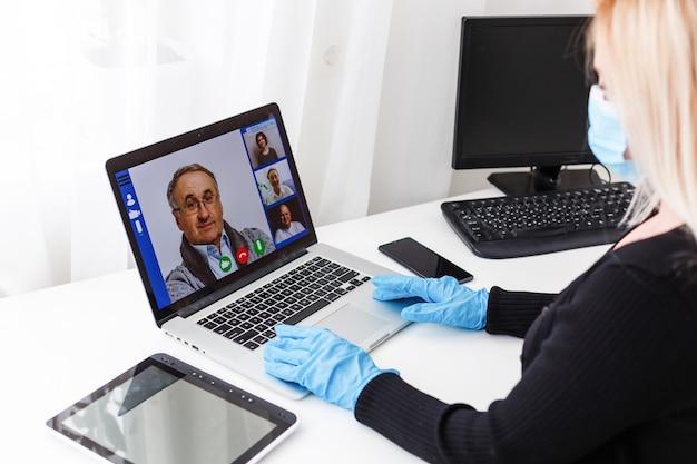 Giovane donna che indossa guanti protettivi sulle mani e maschera sul viso che lavora da casa o al lavoro d'ufficio tramite la videochiamata del laptop per prevenire la diffusione del virus prevenzione della quarantena epidemica