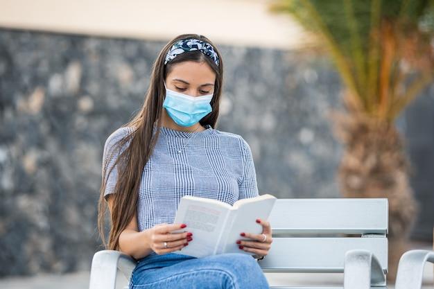 Una giovane donna che indossa una maschera protettiva e legge un libro