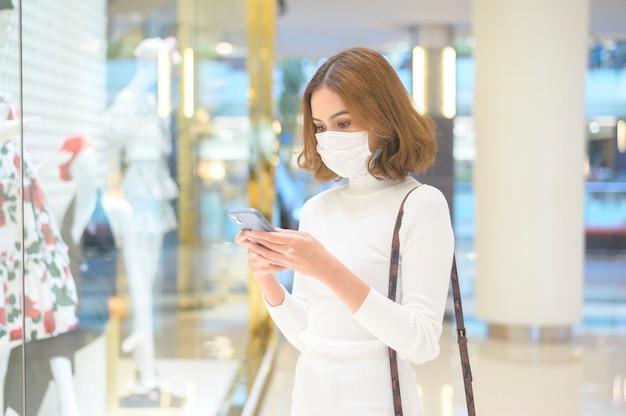Una giovane donna che indossa una maschera protettiva nel centro commerciale, che fa shopping secondo il concetto di pandemia di covid-19.