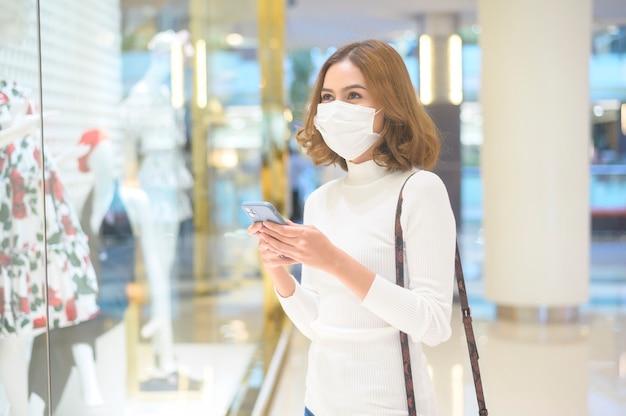 Una giovane donna che indossa una maschera protettiva nel centro commerciale