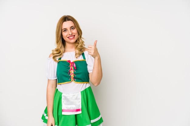 Giovane donna che indossa un giorno di san patrizio vestiti isolati sorridendo e alzando il pollice